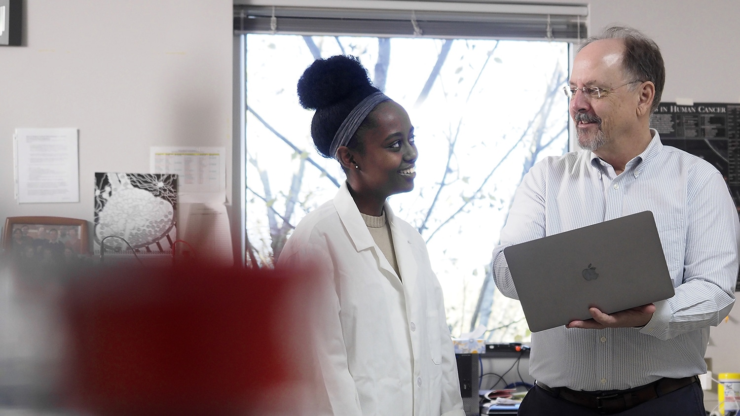 Zoe Lindsey-Mills and Rob Smart review research on a laptop in their lab