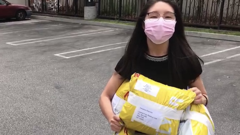 A woman stands in a parking lot wearing a face mask and carrying packages