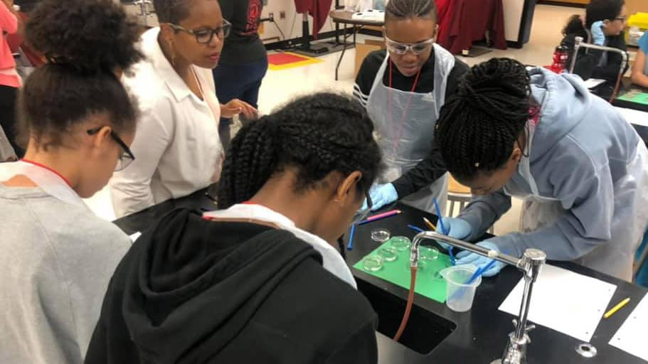 A group of minority students examine a project on a lab table