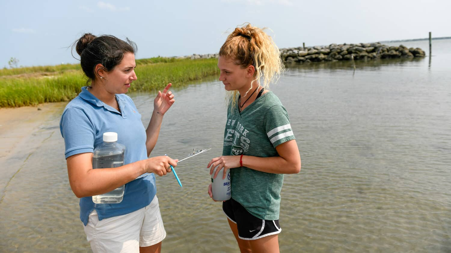 A graduate student and undergraduate student discuss sample collection in shallow water off the N.C. coast