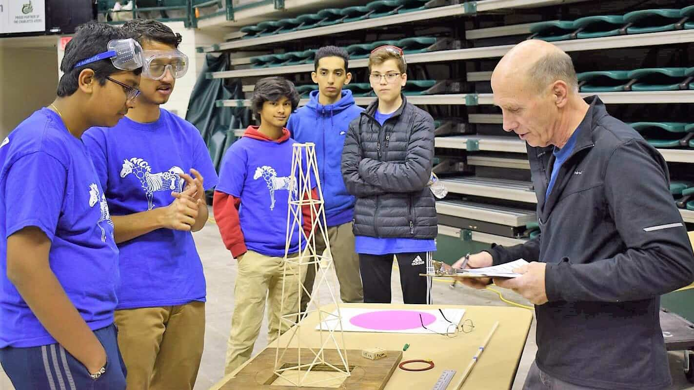 A Science Olympiad team waits while a judge examines their project