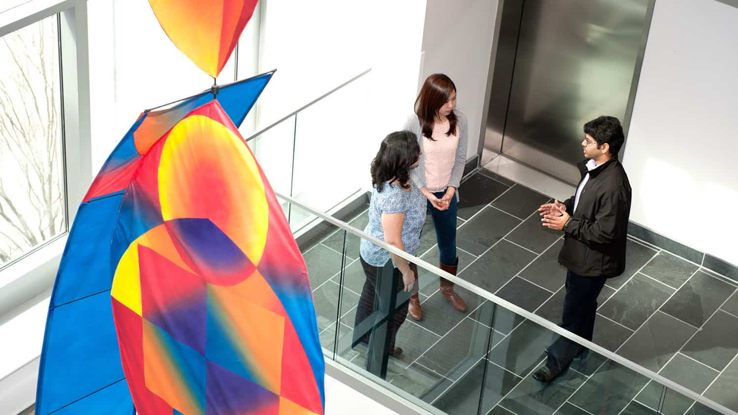 Three people talk in the Atrium of SAS Hall with a colorful art installation in the foreground
